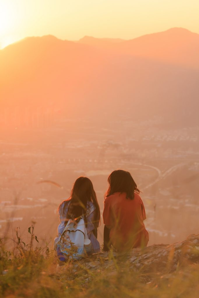 two girls watching beautiful sunset,